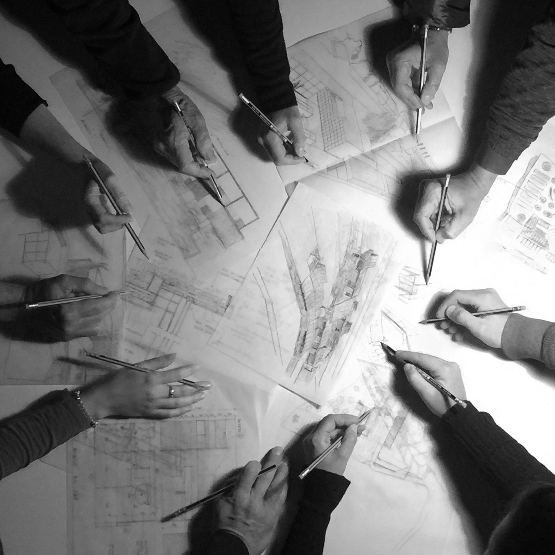 Mani dei componenti dello studio 2CV_A che progettano insieme.