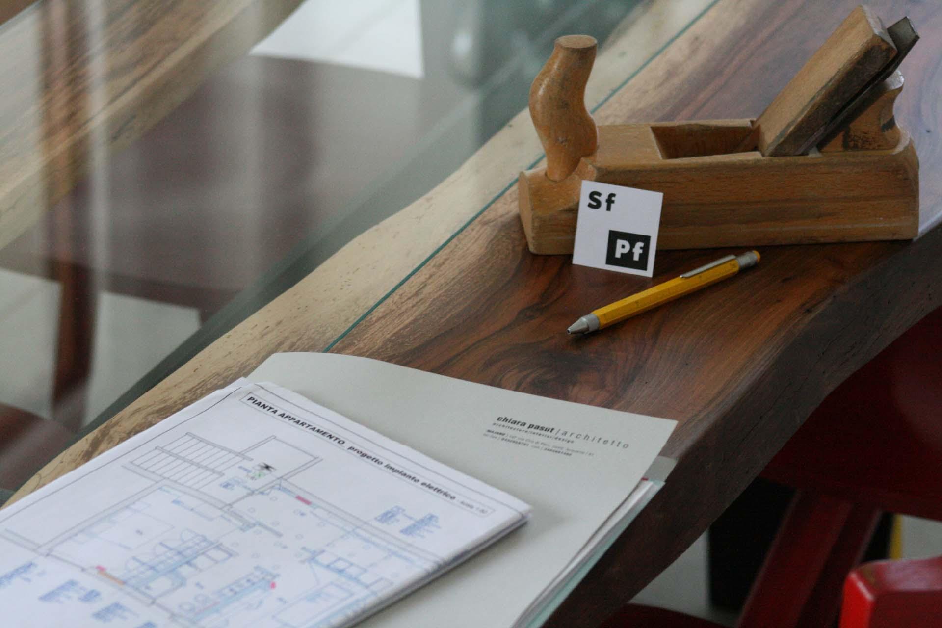 fotografia di un tavolo in legno e vetro con progetto di architettura, pialla, matita