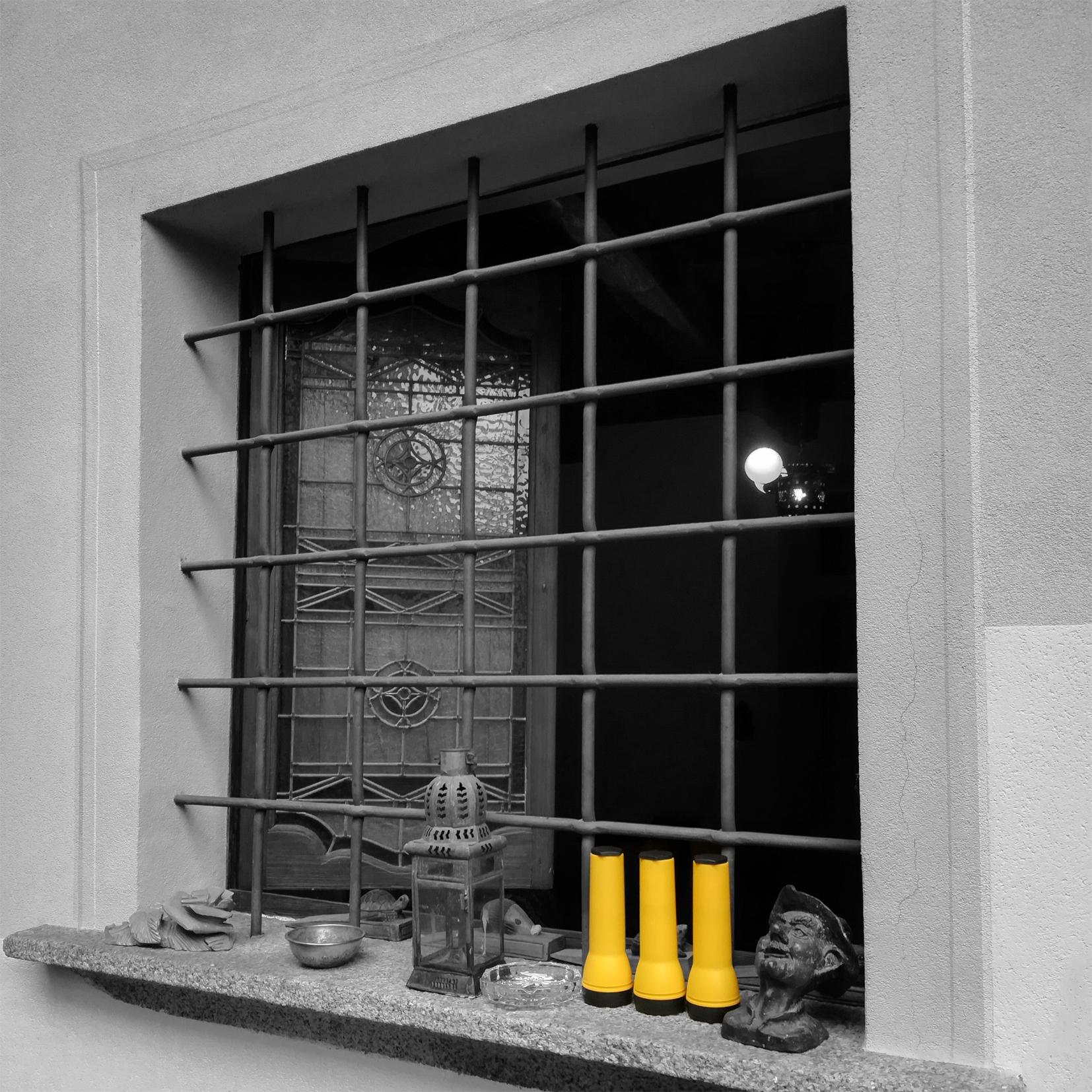 Foto di una finestra della chiesetta con tre torce gialle