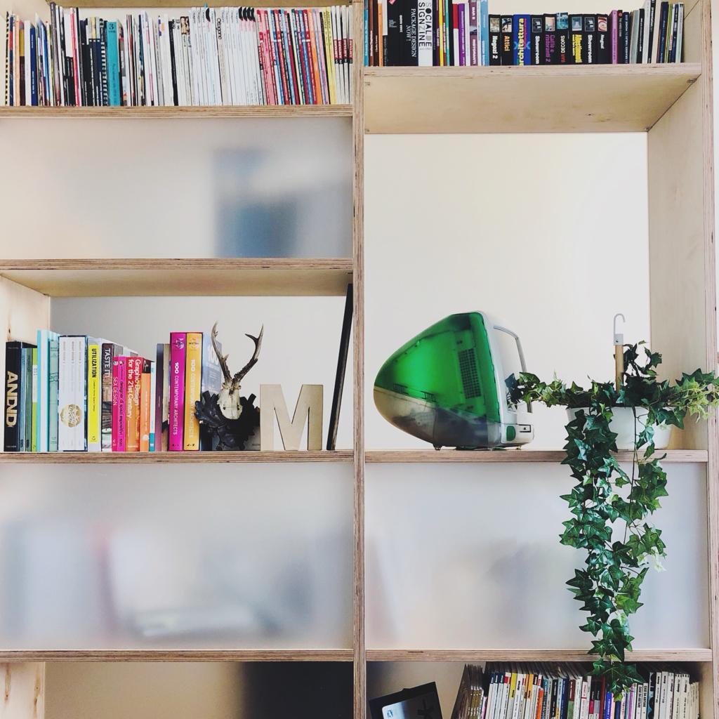 Fotografia di un dettaglio della libreria dello studio con pianta e vecchio Mac.