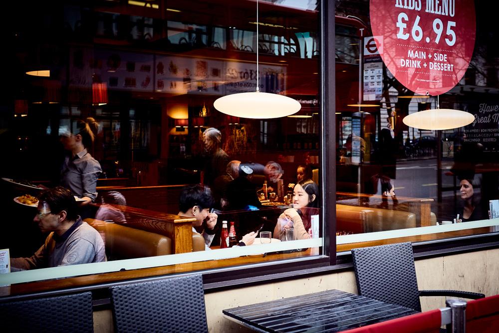 Fotografia di un bar con due ragazze che bevono un caffè guardando dalla vetrina